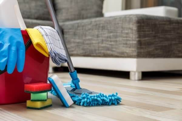 A mop, bucket, sponges, and cloths sit atop a hardwood floor, with a couch in the background