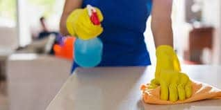 Closeup of maid with yellow rubber gloves spraying and wiping down a countertop