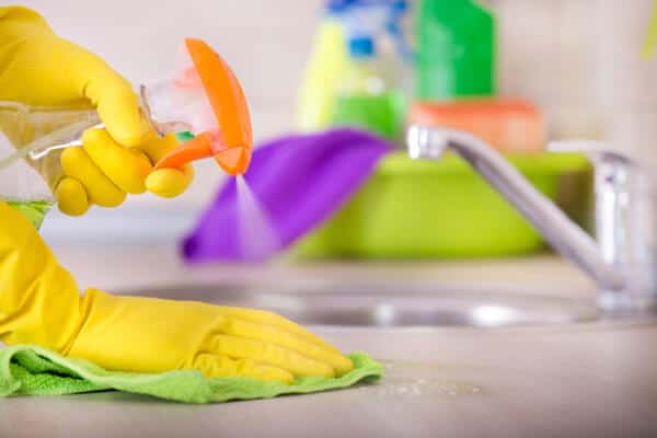 Close up of hand in protective gloves holding cleaning cloth and spray bottle and wiping kitchen countertop. Sink and cleaning supplies in background