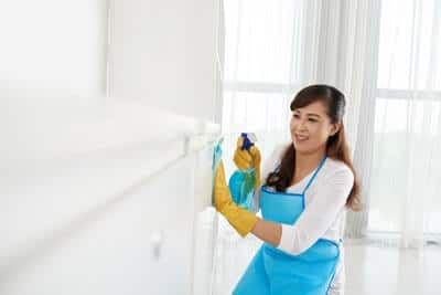 Maid in rubber gloves wiping furniture