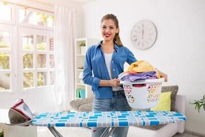 A maid gets ready to put the folded laundry away