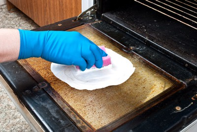 Hand with blue rubber glove cleaning dirty oven