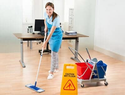 Maid using a sweeper mop to clean wood floors in an office