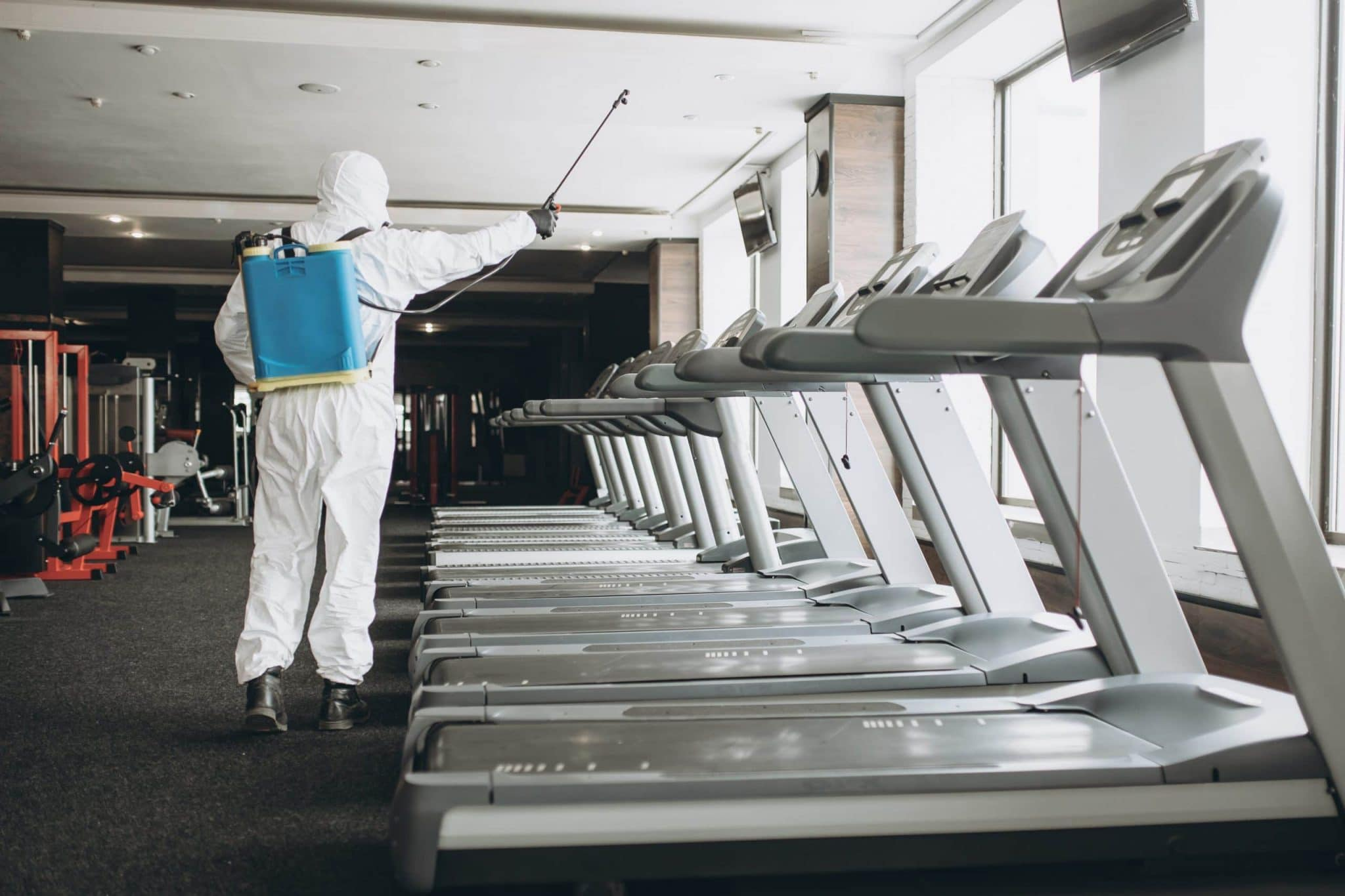 Cleaning and Disinfection in crowded places amid the coronavirus epidemic Gym cleaning and disinfection Infection prevention and control of epidemic. Protective suit and mask and spray bag