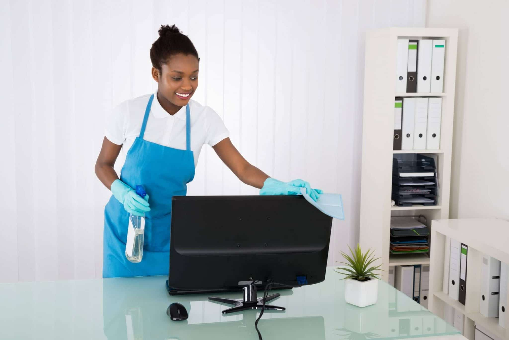 Happy Female Janitor Cleaning Computer With Rag In Office