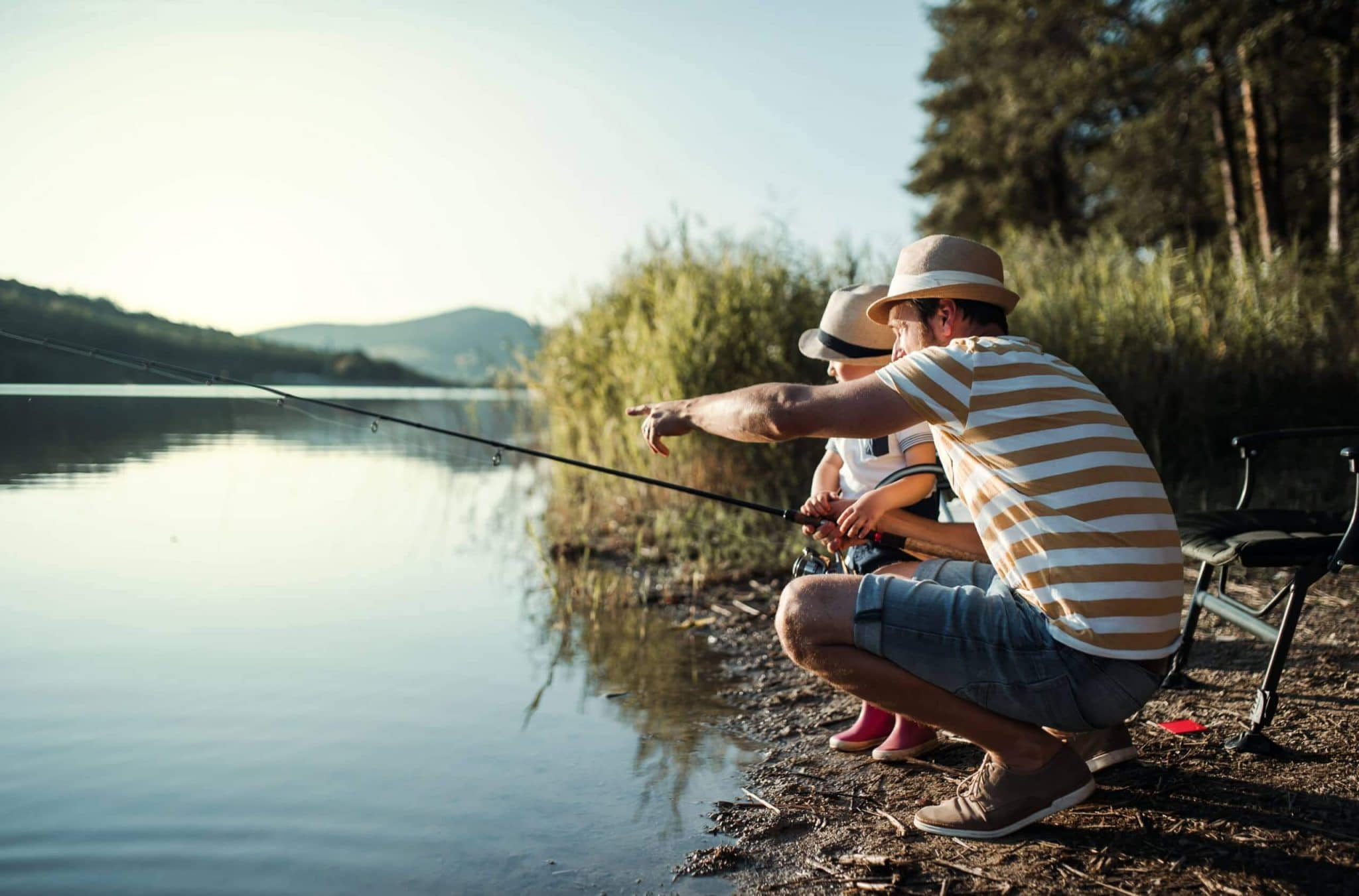 A mature father with a small toddler son outdoors fishing by a river or a lake.